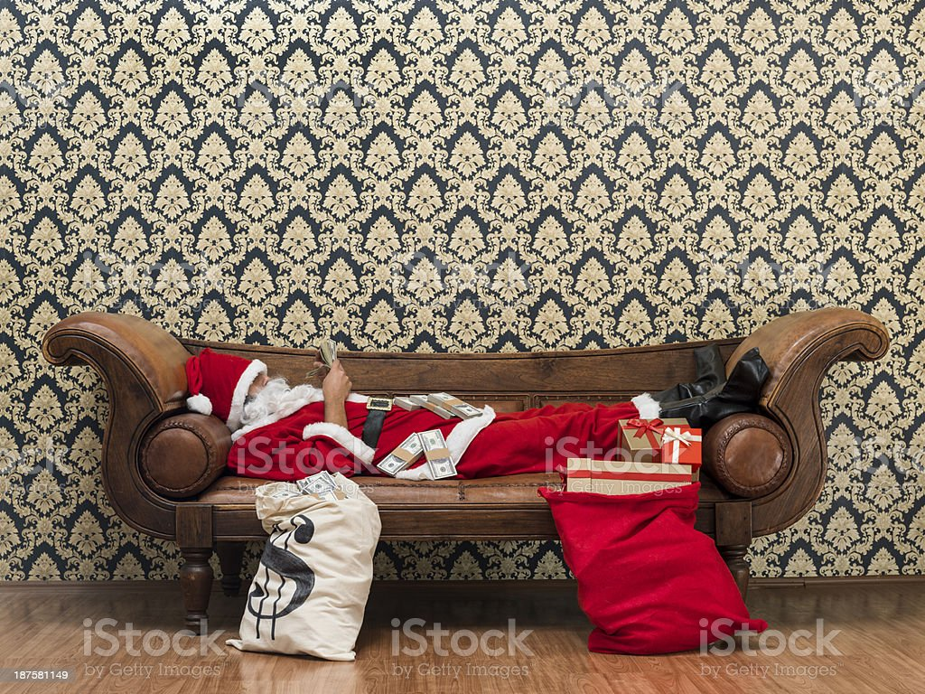 Rich St Nicholas playing with dollar bills royalty-free stock photo