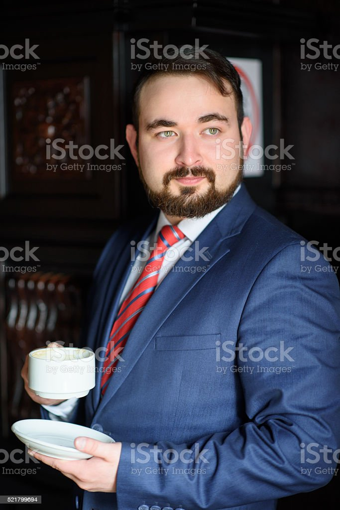 4c0ee0cede Rich successful handsome man in a suit drinking coffee - Stock image .