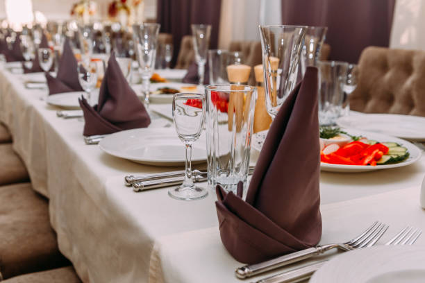 rich table in the restaurant, empty white dishes, glass glasses, Cutlery stock photo