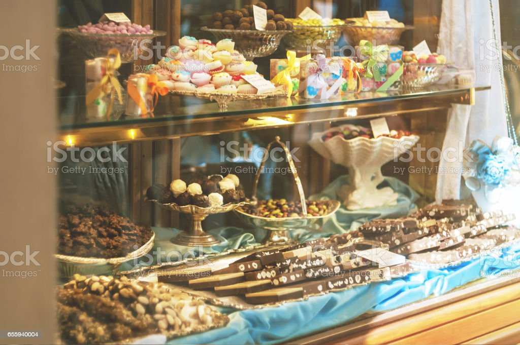 Rich variety of chocolates and candies in display window  of italian pastry shop at sunny day stock photo