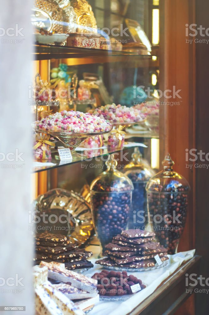 Rich variety of chocolates and candies in display window  of italian pastry shop at sunny day - Photo
