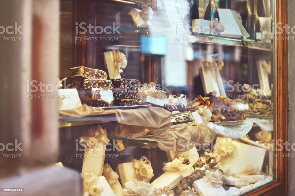 Rich variety of chocolates, candies and biscuits with a gift box in display window of italian pastry shop - Photo