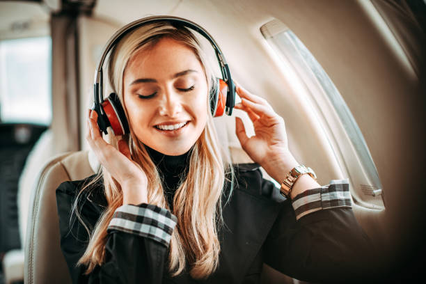 Rich young blonde female model holding her headphones while listening to music in a private airplane stock photo