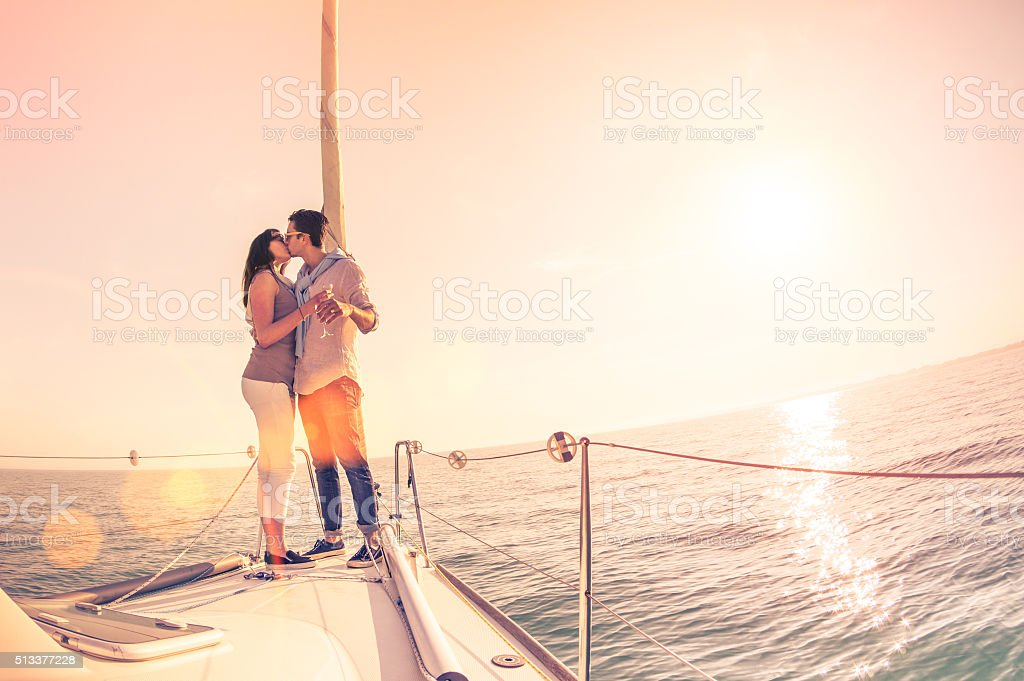 Rich young couple in love on sailboat cheering at sunset stock photo