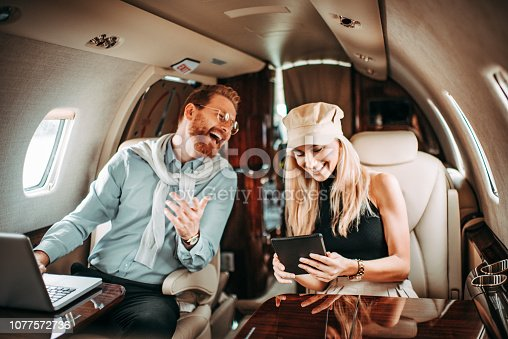 istock Rich young couple laughing together while traveling on a private jet 1077572736