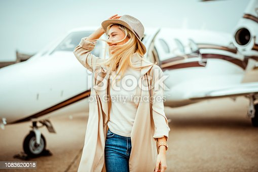Rich blonde girl walking away from a private airplane parked on an airport taxiway. She is smiling and holding her hat.