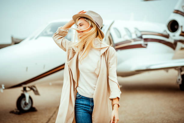 Rich young female walking away from a private airplane parked on an airport taxiway Rich blonde girl walking away from a private airplane parked on an airport taxiway. She is smiling and holding her hat. high society stock pictures, royalty-free photos & images
