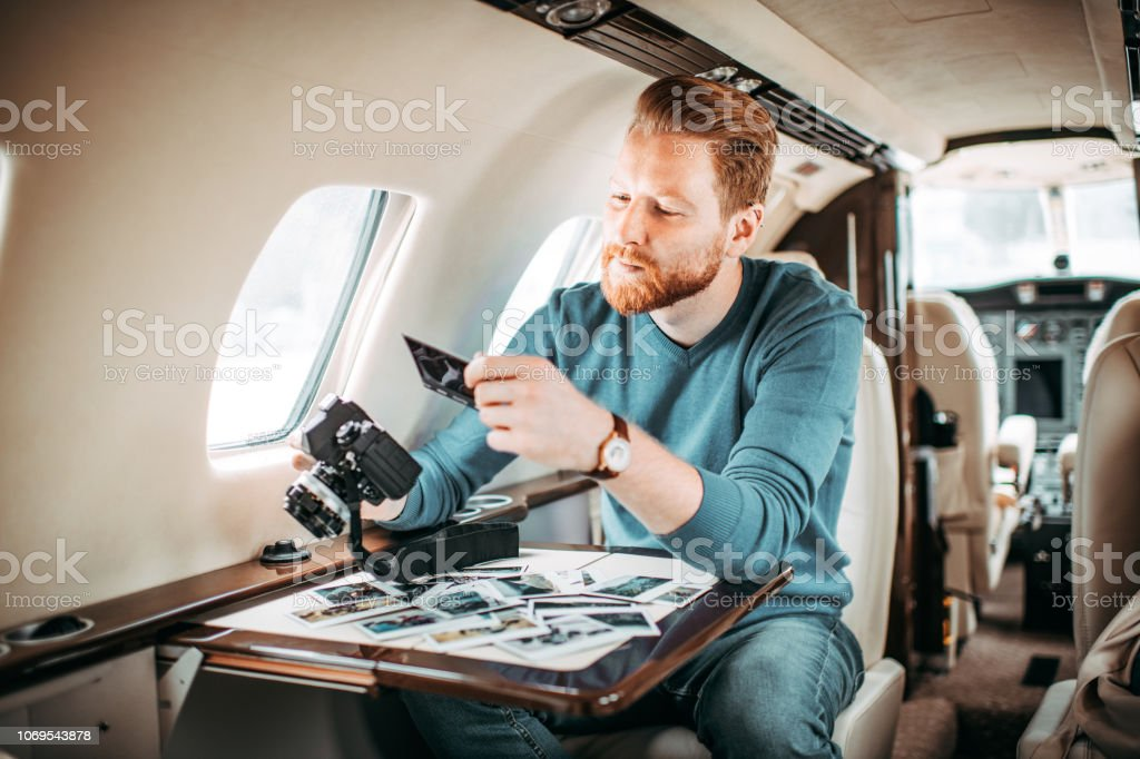 Young successful redheaded man sitting inside a private jet and...