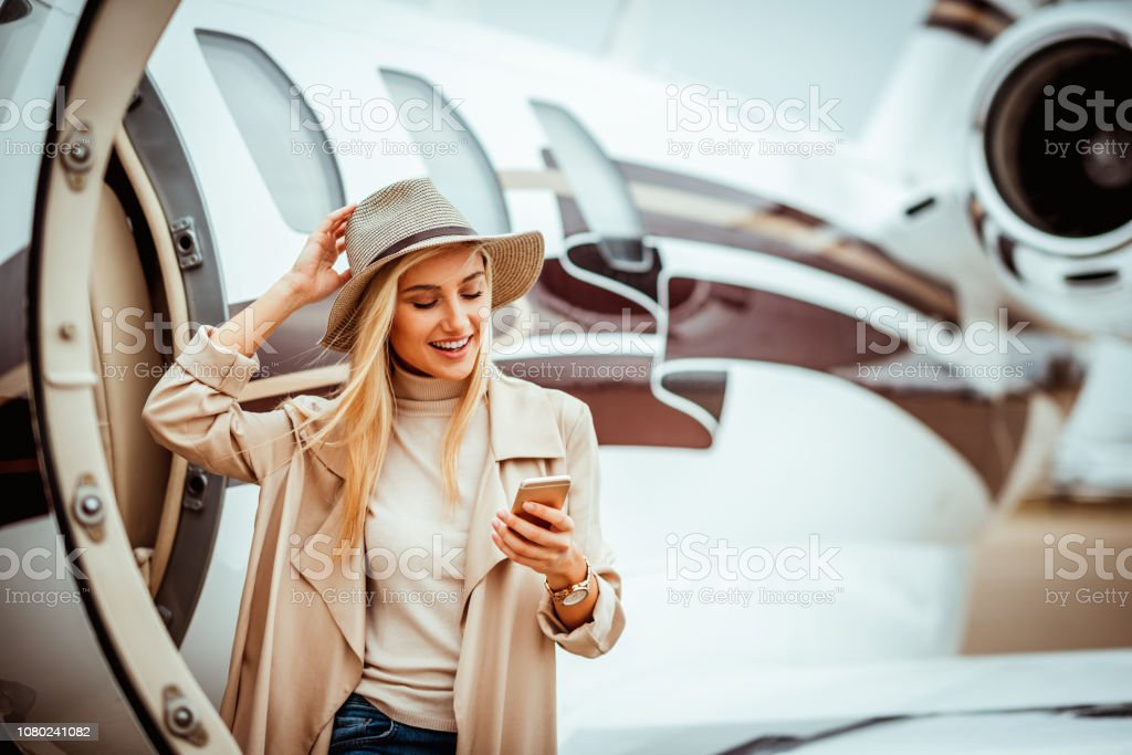 Rich young woman using her mobile phone while exiting a private jet parked on an airport tarmac stock photo