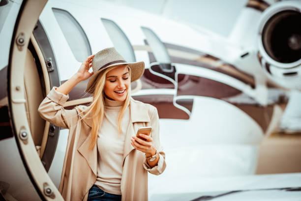 Reiche junge Frau mit ihrem Handy beim Verlassen eines Privatjets auf einem Flughafen Rollfeld geparkt – Foto