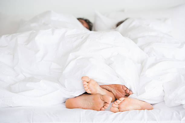 richard & kirstin bed feet -009 - couple in bed stock photos and pictures