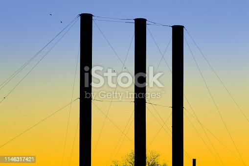 Rickety old smoke stacks held together by many guy-wires, back-lit by this morning's predawn twilight.