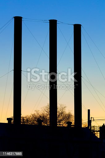 Rickety old smoke stacks held together by many guy-wires.