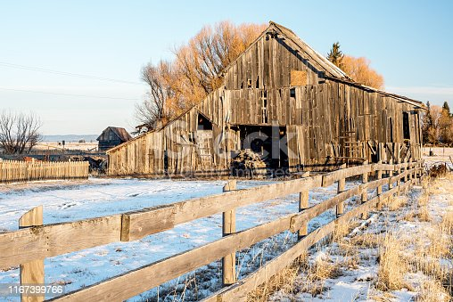 Winter on a farm with a fence and wooden barn