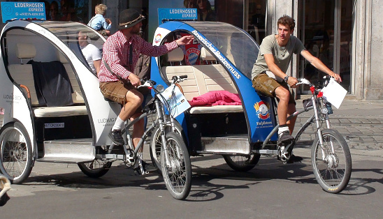 Rickshaw Driver And Tourists Walking Scene In Munich Bavaria Germany. Europe
