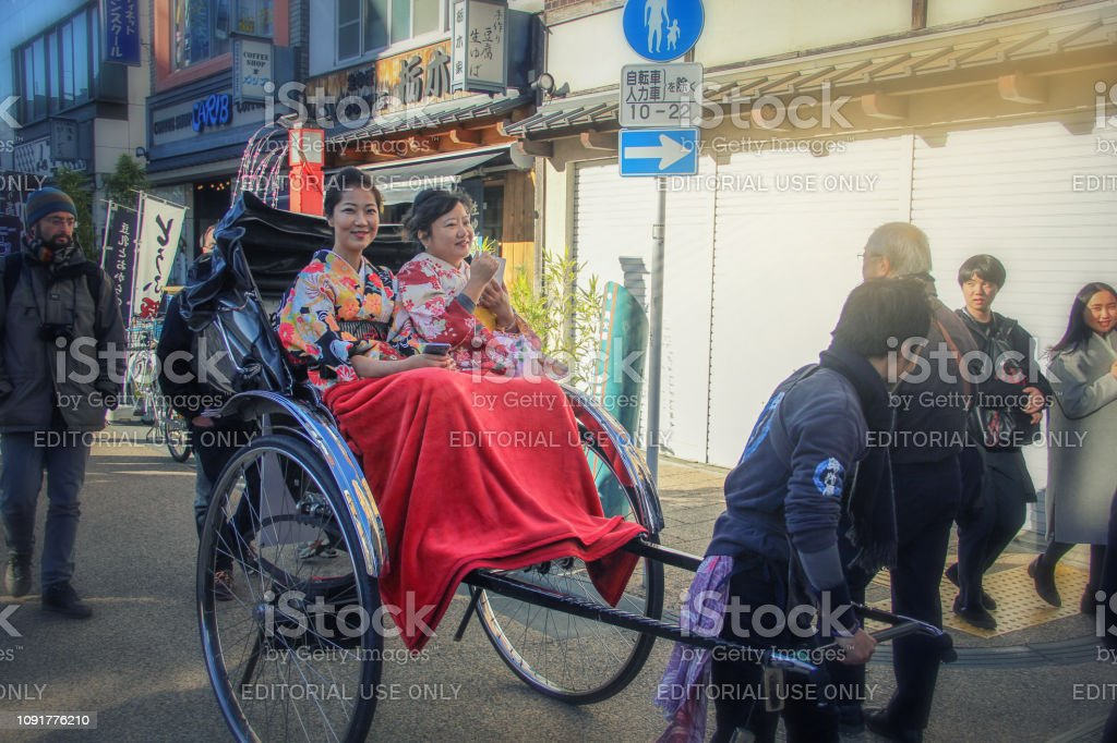 A rickshaw pulls his trolley with two Japanese women dressed in kimono