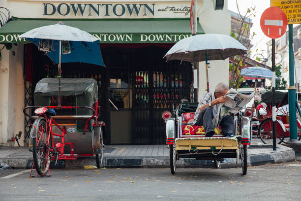 Rickshaw reading a newspaper in George Town, Penang stock photo