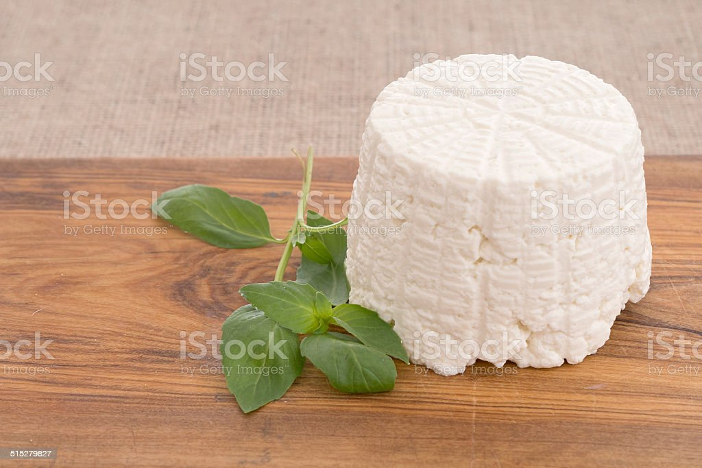 Ricotta cheese, fresh from the mould, mold with basil. stock photo