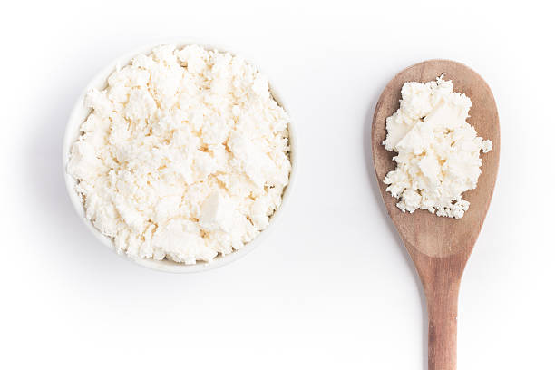 Ricotta Cheese into a bowl Ricotta Cheese into a bowl over a wooden table feta cheese stock pictures, royalty-free photos & images