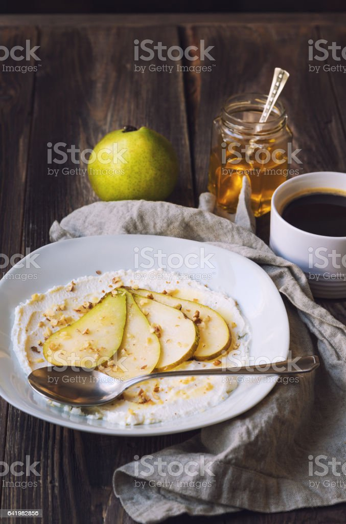 Ricotta cheese with pear,crushed walnuts and honey on rustic wooden background stock photo