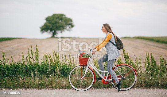 Young woman riding a bike through the countryside with flowers in the bicycle basket