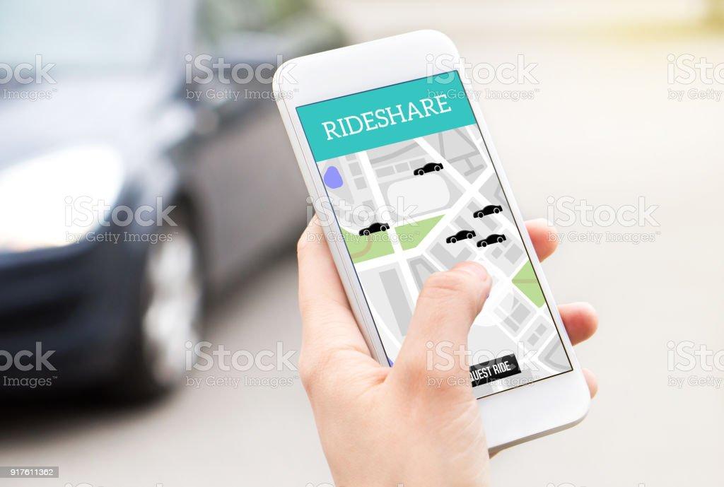 Paseo compartido servicio de taxi en la pantalla del smartphone. Transporte compartido en línea de la aplicación y compartir aplicación móvil. Mujer sosteniendo el teléfono con un coche en el fondo. - foto de stock