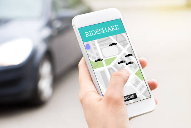 ride share taxi service on smartphone screen. online rideshare app and carpool mobile application. woman holding phone with a car in the background. - rideshare stock photos and pictures