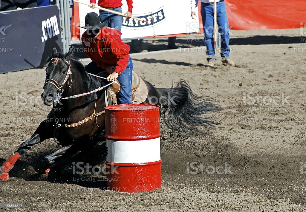 Rider and horse round a barrel in rodeo event stock photo