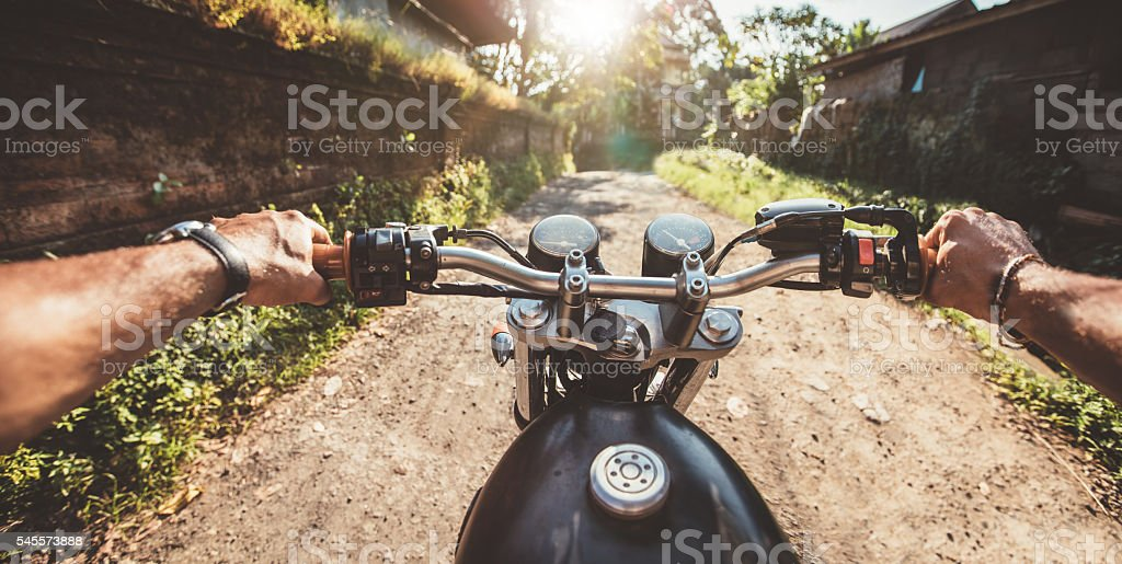 Rider driving motorcycle on a rural road stock photo