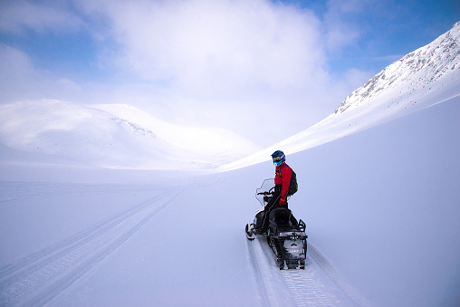 Rider -  instructor on   snowmobile in winter mountain pass  in  Khibiny Mountains,  Kola Peninsula, Russia