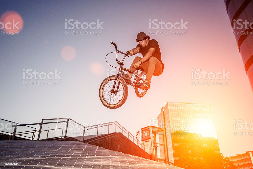 BMX rider jumping in urban environment stock photo