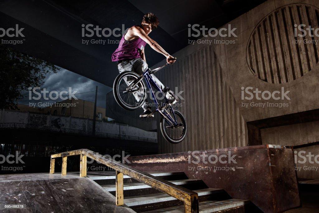 rider jumping on his bike in skatepark stock photo