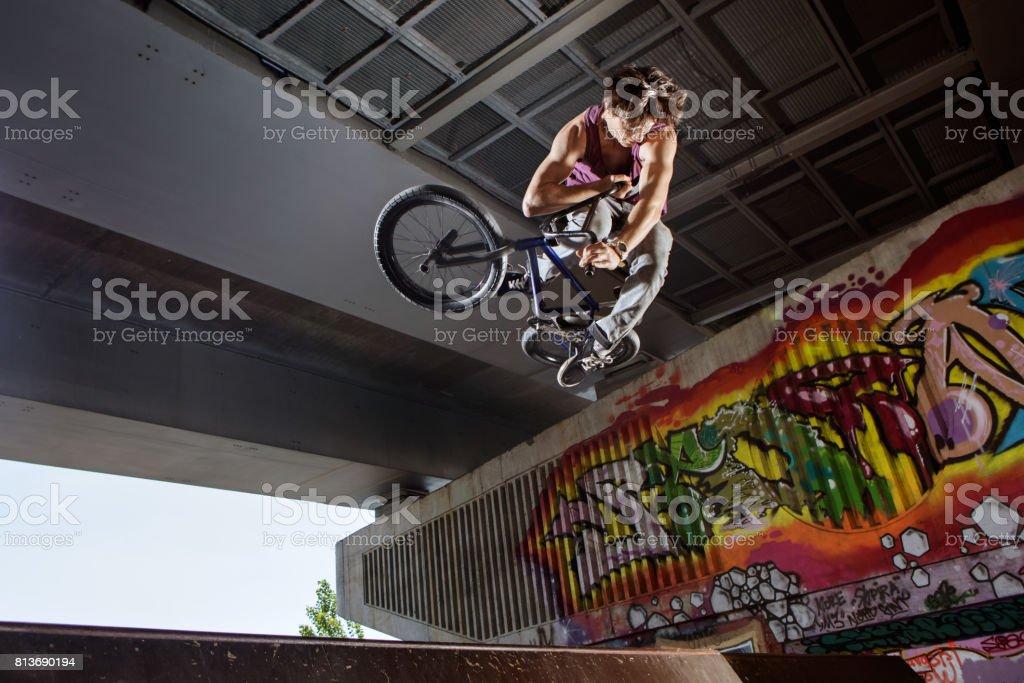 BMX rider jumping on his bike in skatepark stock photo