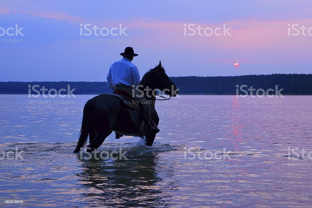 Rider on a horse watching the sunrise royalty-free stock photo