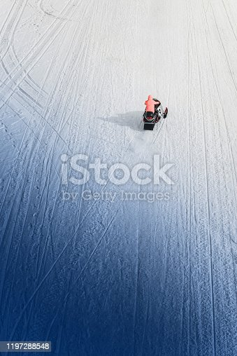 Rider on a snowmobile in a coral jacket rides on a snowy road, top view from a quadcopter