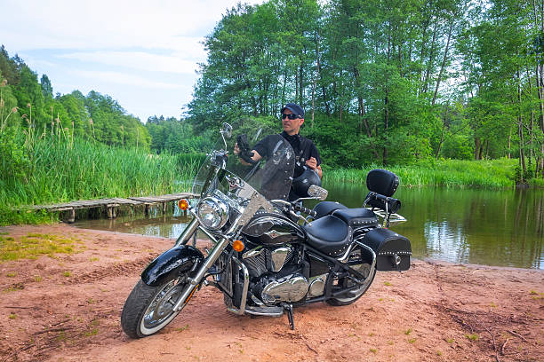 Rider on the shores of the river Drawa, Poland Drawsko Pomorskie, Poland - June 06,2015: Black dressed adult man stands on the shores of the river Drawa and prepares to ride the heavy customized Kawasaki , Zachodniopomorskie province, Poland  kawasaki heavy industries stock pictures, royalty-free photos & images