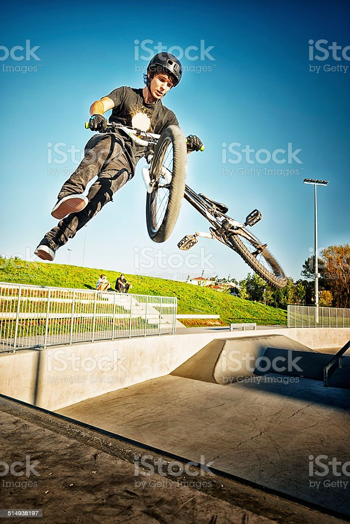 BMX biker performing a stunt in ramp park.