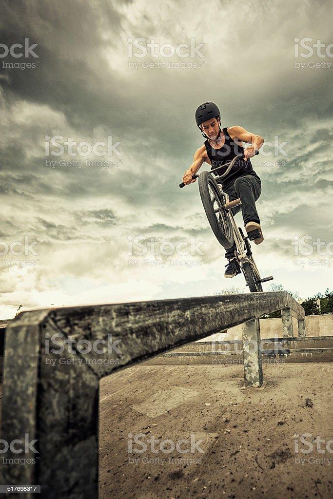 BMX rider performing tricks in ramp park.