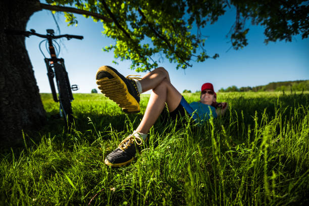 Rider with the bicycle Lady relaxing in the shadow of big tree after cycling female biker resting stock pictures, royalty-free photos & images
