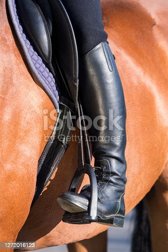 A woman's booted foot standing in a black stirrup of horse saddle.