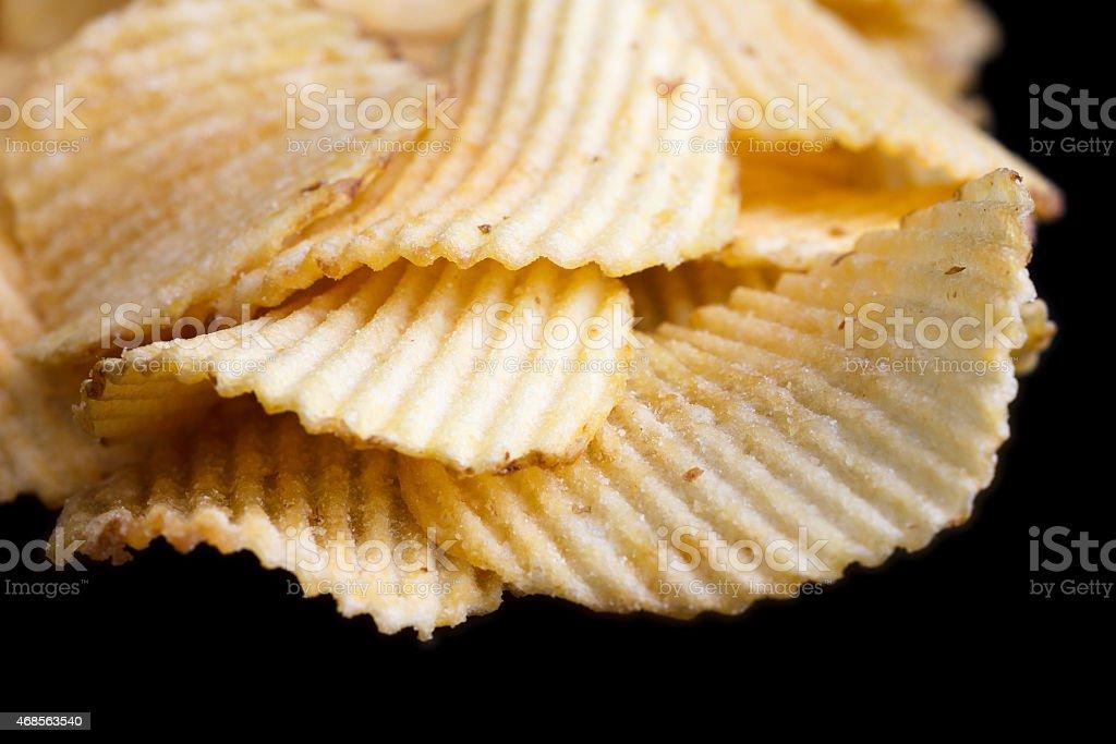 Ridged fried potato crisps on black. stock photo