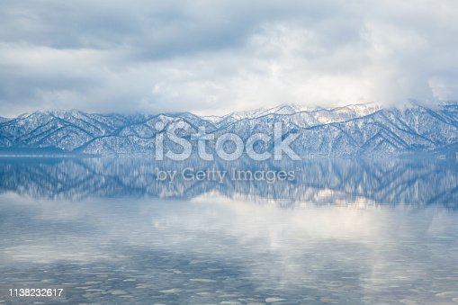 Smooth, shallow waters reflect the ridges and trees of distant snow covered mountains. Mirror-calm reflective water.