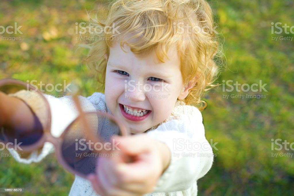 Ridiculous little girl puts on big sunglasses royalty-free stock photo