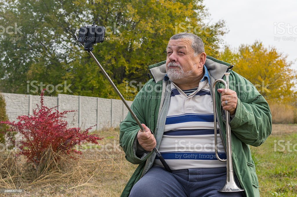 Ridiculous senior man making faces while doing selfie stock photo
