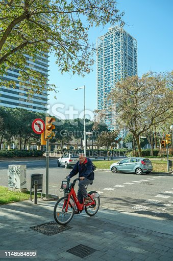 Barcelona, Spain, March 23, 2019 - People riding a bicycle in Barcelona Marina area in a clear spring day.