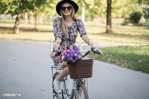 Young beautiful woman riding a bicycle in a park on a sunny day