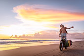 One man, handsome hippie surfer riding a motorcycle on the beach in sunset.