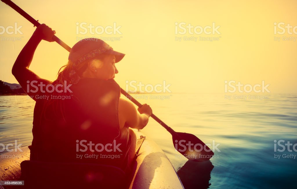 Riding a kayak on sea at sunset stock photo