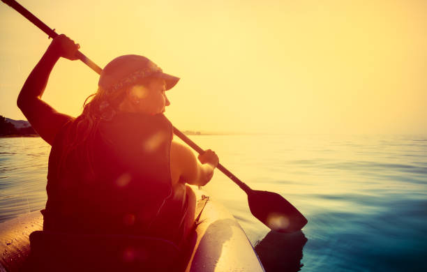 riding a kayak on sea at sunset - young singles stock photos and pictures