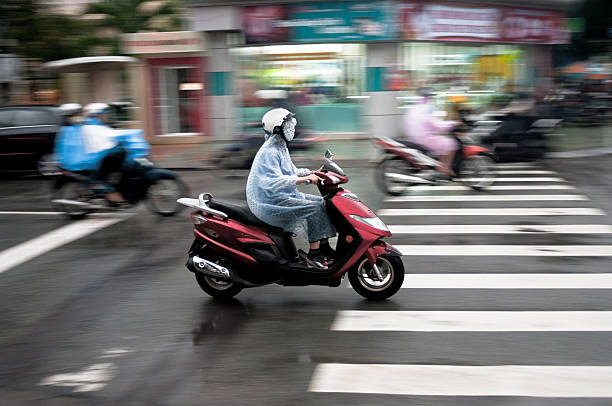 riding a motorcycle in through rain in nha trang, vietnam - motorbike, umbrella stock pictures, royalty-free photos & images